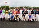 Three-year-old Brayden Cecchi and his father are joined in the winner's circle by the jockey colony at Arlington Park June 29.