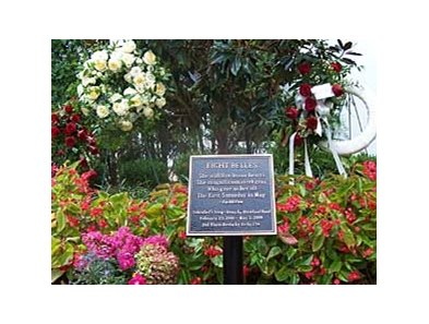 Flowers surround the Eight Belles memorial plaque in the gardens of the Kentucky Derby Museum.