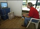 Trainer Dallas Stewart watches television coverage of Hurricane Katrina in his tack room at Saratoga.