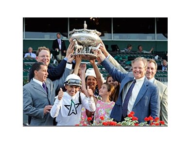 Bill Mott celebrates his Belmont victory in the winner's circle.