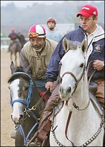 Rockport Harbor, left, accompanied by trainer John Servis on pony, at Oaklawn Park Wednesday.