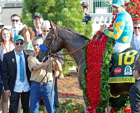 American Pharaoh and jockey Victor Espinoza are adorned with a blanket of roses.