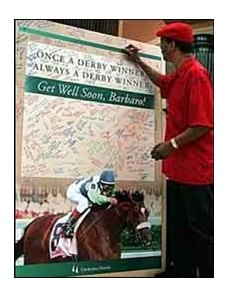 A fan signs his get well wishes to one of two oversized cards set up at Churchill Downs.