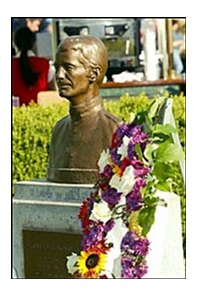 A floral wreath is placed beside a bust of Hall of Fame jockey Bill Shoemaker at Santa Anita Park.