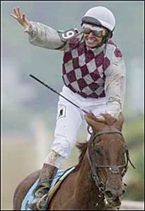 Jose Santos, with his hand open to show there is nothing there, celebrates atop Funny Cide after winning the Preakness.