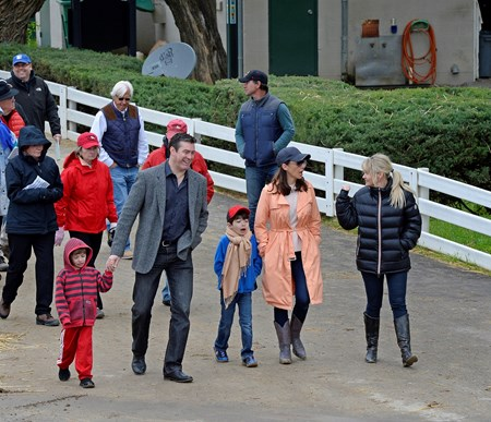 Caption: Jill Baffert, right, with family and connections as husband, trainer Bob Baffert, walks behind them.