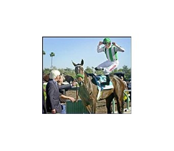 David Flores leaps off Atlantic Ocean as trainer Bob Baffert watches in the winner's circle after their win in the $250,000 John Deere Oaks at Santa Anita.