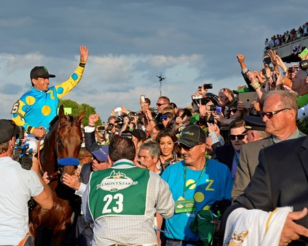 American Pharoah and Victor Espinoza are lead in to the winner's circle.