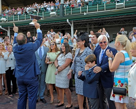 Caption: Zayat raises Triple Crown trophy and says number one to crowd