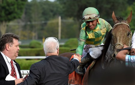 Jockey Javier Castellano is congratulated by Donegal Racing's Jerry Crawford, center, and trainer Dale Roman's, left  after winning the 146th running of the Travers Stakes Saturday evening Aug. 29, 2015 at the Saratoga Race Course in Saratoga Springs, N.Y.
