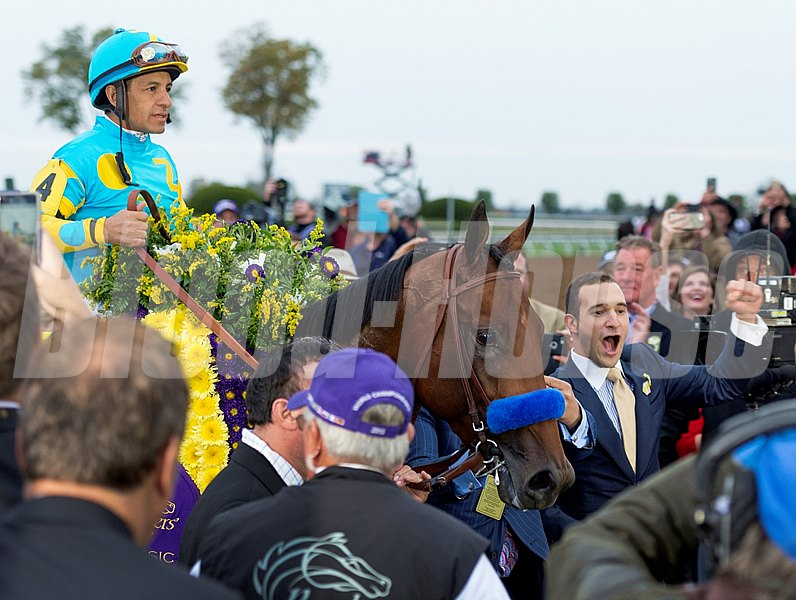 American Pharoah and jockey Victor Espinoza are crowned with flowers.