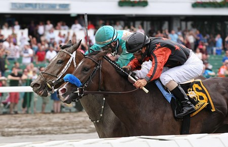 She's Hot Wired #4 (L) and Trevor McCarthy pass 2nd place finisher Bustin Out #6 and Jose Ferrer at the finish line to win the Open Mind Handicap at Monmouth Park in Oceanport, New Jersey on Monday May 30, 2016.