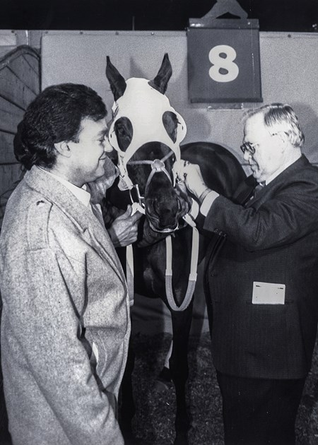 Buddy Ryan takes time to help 1988 trainer champ Joe Orseno saddle Rocketette for the 3rd race at Garden State Park. February 1989