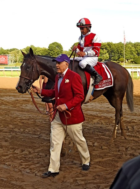 Rick Porter, owner leads Songbird  and Mike Smith to the winner's circle after winning the 100th running of The Coaching Club American Oaks
