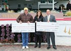 Rick Hiles of the Kentucky HBPA and Mike Ziegler of Churchill Downs present checks to Ashton Moynihan of Thoroughbred Aftercare Alliance.