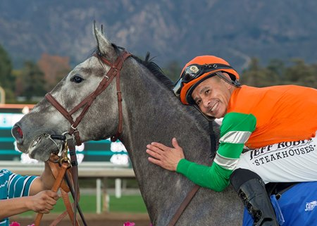 Hall of Fame jockey Mike Smith poses aboard Unique Bella in the Santa Anita Park winner's circle