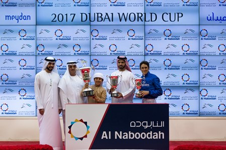 Sheikh Mohammad bin Mansoor bin Zayed Al Nahyan, Saeed bin Suroor and Christophe Soumillon accept the trophy for the UAE Derby