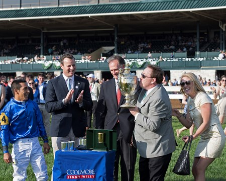 l-r, Paco Lopez, David Wachman, Jimmy Bell, look on as trainer Kiaran McLaughlin lifts and kisses the trophy. Daughter Erin McLaughlin on right reacts.Dickinson with Paco Lopez up wins The 29th Running of The Coolmore Jenny Wiley (G1) at Keeneland on April 15, 2017 Keeneland in Lexington, Ky.
