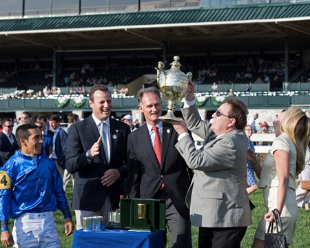 l-r, Paco Lopez, David Wachman, Jimmy Bell, look on as trainer Kiaran McLaughlin lifts and kisses the trophy. Daughter Erin McLaughlin on right reacts. Dickinson with Paco Lopez up wins The 29th Running of The Coolmore Jenny Wiley (G1) at Keeneland on April 15, 2017 Keeneland in Lexington, Ky.