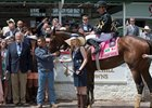 Erin Kelley, daughter of Calumet Farm owner Brad Kelley, holds Wild Shot in the winner's circle