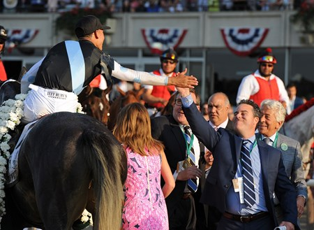 "Majority owner Aron Wellman gives a ""high5"" to jockey Jose Ortiz after winning the 149th Belmont Stakes on Tapwrit"