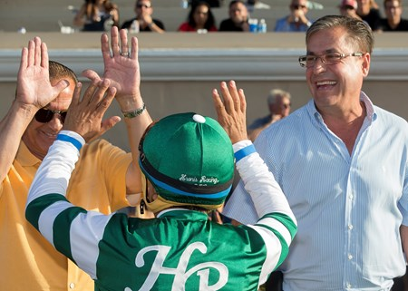 Owner Kosta Hronis, left, and trainer John Sadler, right, celebrate with jockey Victor Espinoza, center, after Accelerate's victory in the 2017 San Diego Handicap