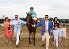 Jay Hanley (left) and Sol Kumin (right) lead Lady Eli and Irad Ortiz Jr. to the winner's circle with their families
