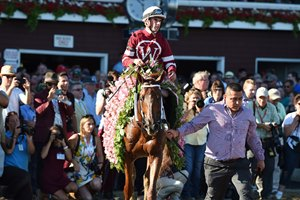 Gun Runner wears the garland of flowers he earned in the Whitney Stakes