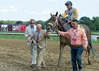 Charles Fipke (left, holding shank) leads Forever Unbridled into the winner's circle as Dallas Stewart (left) looks on