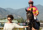Owner Ramona Bass leads Avenge, with Flavien Prat, into the winner's circle after the Rodeo Drive Stakes