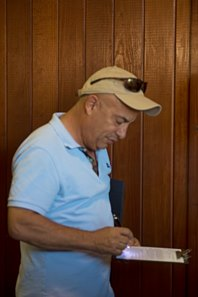 Mark Casse signs the ticket for Hip 126, a Violence colt that topped the Oct. 10 first session of the OBS yearling sale