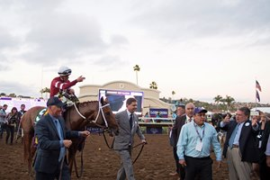 Assistant Scott Blasi (left) and co-owner Ron Winchell (right) lead Gun Runner and Florent Geroux into the winner's circle at Del Mar