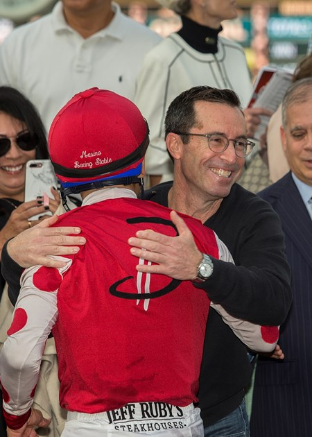 Co-owner Jeff Bloom of Bloom Racing Stable, right, has a hug for jockey Mike Smith, left, in the winner's circle after Midnight Bisou's victory in the 2018 Santa Ynez Stakes (G2), Sunday, January 7, 2018 at Santa Anita Park, Arcadia CA.