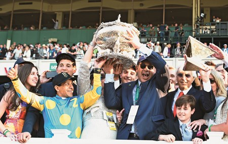 American Pharoah's owner Ahmed Zayat holds the Belmont Stakes Trophy aloft, center with the help of jockey Victor Espinoza, left as trainer Bob Baffert raises the Triple Crown trophy aloft after his trainee made his way to the record books by winning the 147th running of the Belmont Stakes and thoroughbred racing's Triple Crown June 6, 2015 at Belmont Park in Elmont, N.Y.