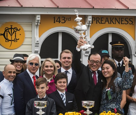 Teo Ah Khing holds the winner's trophy aloft after Justify wins the 143rd running of the Preakness Stakes