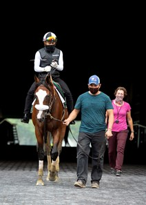 ELMONT, NY-Sackatoga Stable's Tiz the Law, and trained by Barclay Tagg, walks out of the tunnel, after breezing five furlongs after the break with Manny Franco in the irons, Wednesday, July 8, 2020, with Juan Baraja Saldana, foreman/groom, and assistant trainer Robin Smullen.